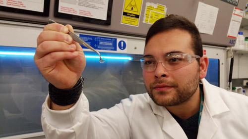 Berkay Ozcelik holding up an implant.